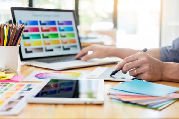 Mediengestalterin wählt am Laptop Farben und Grafiken für Layout