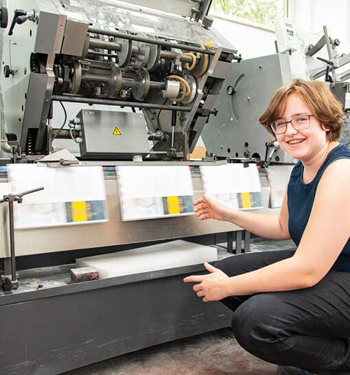 Mitarbeiterin der Druckverarbeitung an einer Falzmaschine